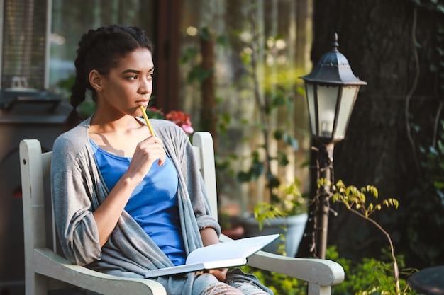 Hermosa niña africana escribiendo en el cuaderno