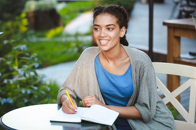Hermosa niña africana sonriente escribiendo en el cuaderno