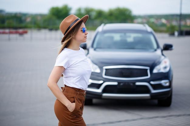 Una hermosa niña de apariencia europea con gafas y un sombrero marrón está parada cerca de un automóvil negro.