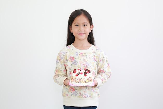 Hermosa niña asiática niño sosteniendo pastel de feliz cumpleaños sobre fondo blanco.