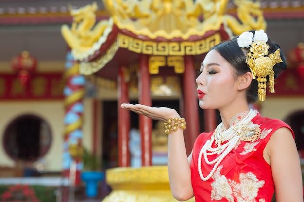 Una hermosa niña asiática vestida con un traje rojo