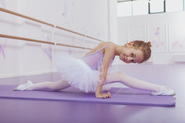Hermosa niña bailarina haciendo divisiones, haciendo ejercicio en el estudio de baile