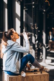 Hermosa niña bebía agua de una botella de plástico, cálida mañana soleada dentro de la habitación