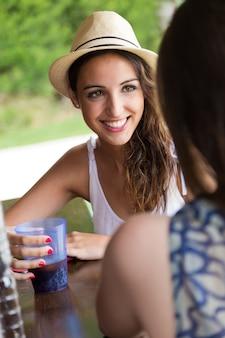 Hermosa niña bebiendo en el bar de la piscina con un amigo.