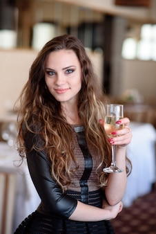 Una hermosa niña está bebiendo champán en un restaurante.