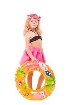 Hermosa niña en bikini negro, falda rosa y corona rosa detrás del anillo de goma