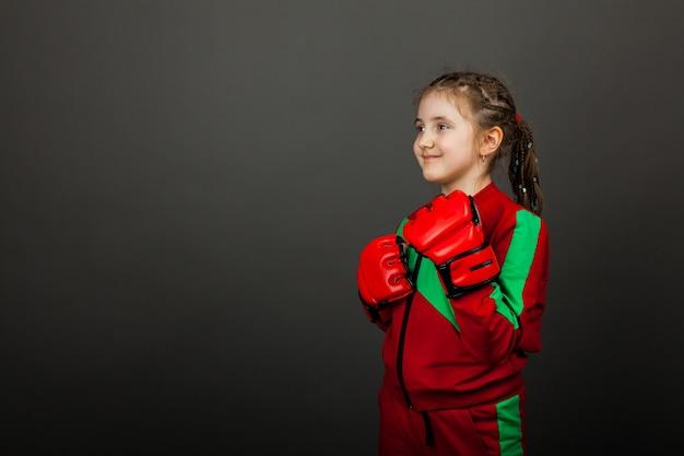 Hermosa niña boxer en guantes listos para luchar.