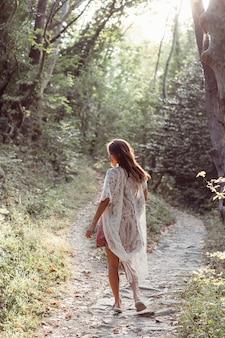 Hermosa niña camina al pie de la montaña a lo largo