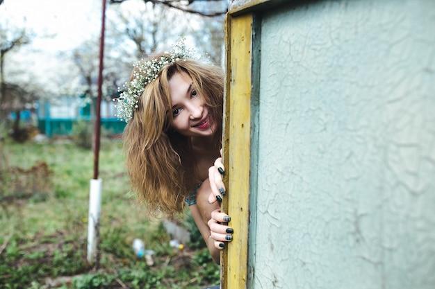 Hermosa niña camina en el exuberante jardín vestida con una corona