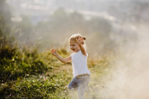 Hermosa niña en camisa blanca y pantalones vaqueros se ejecuta en el césped en la niebla con gran paisaje