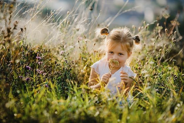 Hermosa niña en camisa blanca y pantalones vaqueros se sienta en el césped con gran paisaje