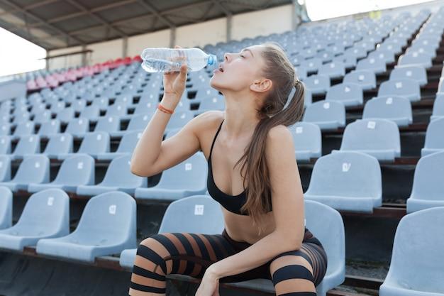 Hermosa niña caucásica atleta tiene en sus manos un agua en una botella de plástico