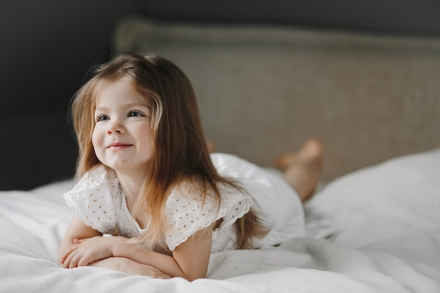 Hermosa niña caucásica pequeña está acostada en la cama blanca vestida con un vestido blanco y sonriendo, y mirando hacia un lado