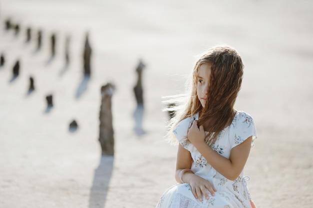 Hermosa niña caucásica en el suelo seco en las vacaciones de verano sola en vestido blanco está mirando a un lado, infancia feliz