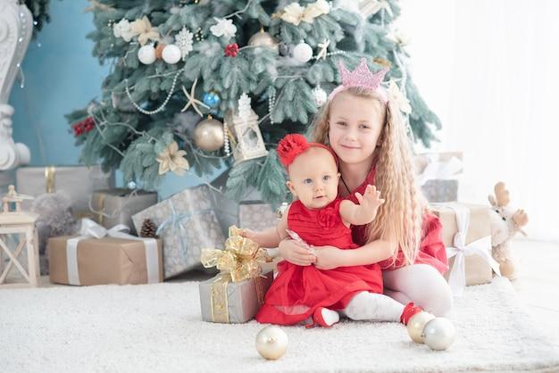 Hermosa niña cerca de árbol de navidad decorado