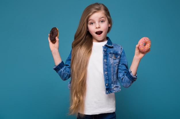 Hermosa niña en chaqueta de jean con largo cabello castaño mantenga masa