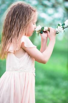 Hermosa niña disfrutando el olor en un jardín floreciente de primavera