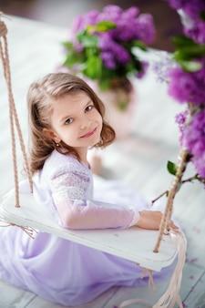 Hermosa niña en edad preescolar con un delicado vestido sentado en un columpio decorado con flores de color lila