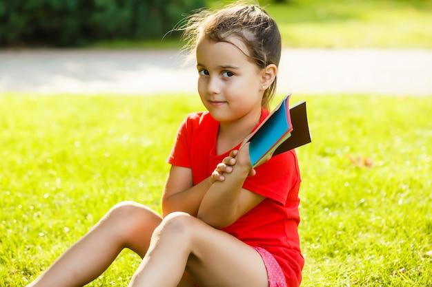 Hermosa niña elige un color de pintura en la paleta de colores
