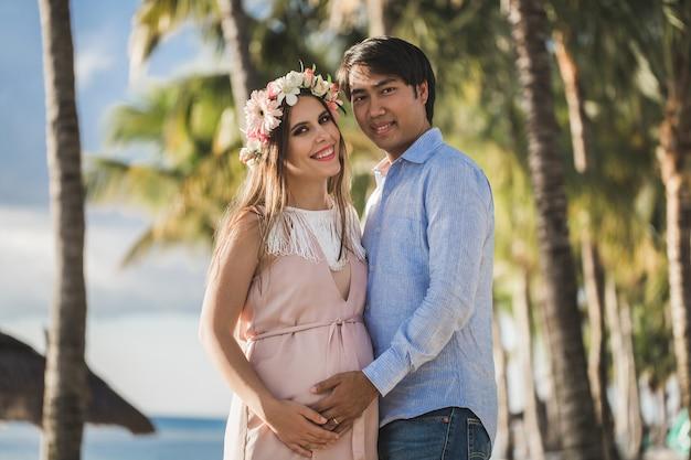 Hermosa niña embarazada y hombre en la playa