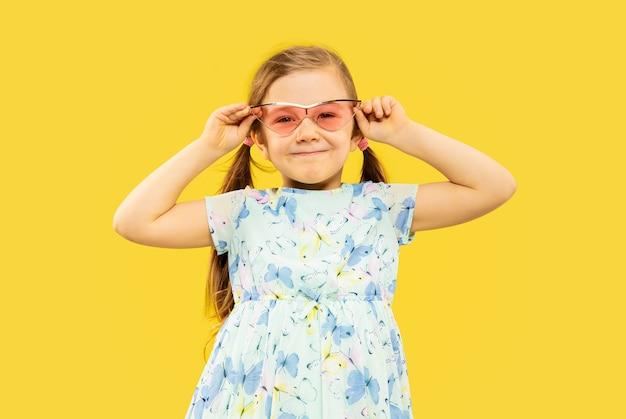 Hermosa niña emocional aislada en amarillo