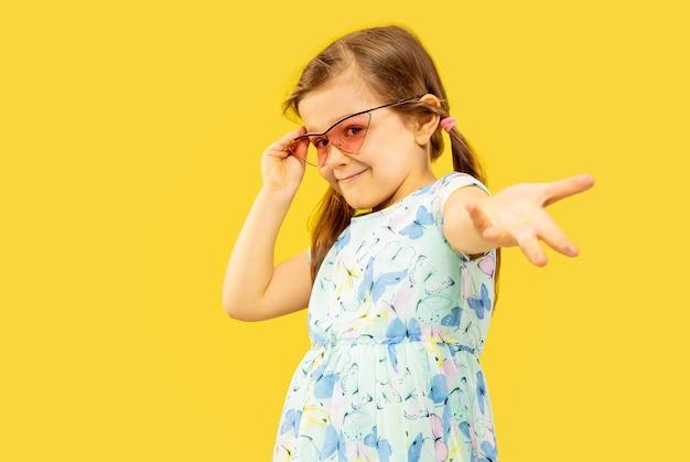 Hermosa niña emocional aislada sobre fondo amarillo. retrato de medio cuerpo de un niño feliz de pie y con un vestido y gafas de sol rojas. concepto de verano, emociones humanas, infancia.