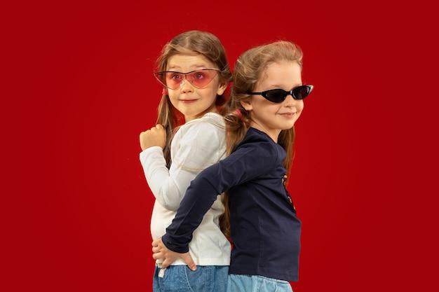 Hermosa niña emocional aislada sobre fondo rojo. retrato de medio cuerpo de hermanas felices o amigos con gafas de sol rojas y negras. concepto de expresión facial, emociones humanas, infancia.
