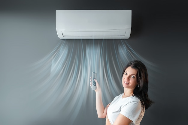 Una hermosa niña se encuentra bajo el aire acondicionado y una corriente de aire fresco y frío contra una pared gris. el concepto de calor, aire frío, enfriamiento, frescura.
