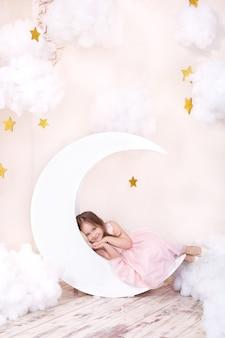Hermosa niña se encuentra en estudio con decoración de luna, estrellas y nubes. el niño está soñando. niña linda se sienta en una luna decorativa con nubes de algodón y estrellas. concepto de sueño saludable infancia