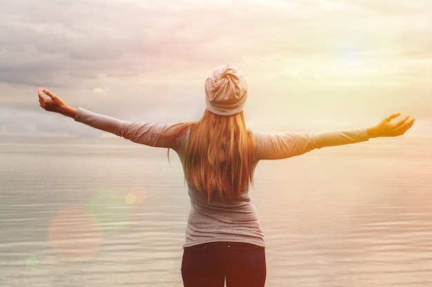 Una hermosa niña se encuentra en la orilla del mar. manos arriba. puesta de sol. clases de yoga.