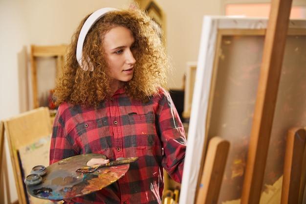 Hermosa niña escucha música a través de auriculares y dibuja una pintura
