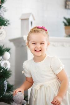 Hermosa niña esperando un milagro en adornos navideños