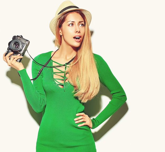 Hermosa niña feliz linda mujer rubia en ropa casual verano verde hipster toma fotos con cámara fotográfica retro