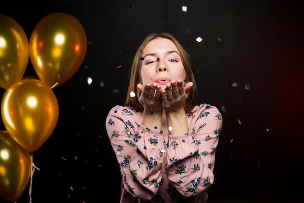 Hermosa niña feliz que sopla un beso y globos de oro