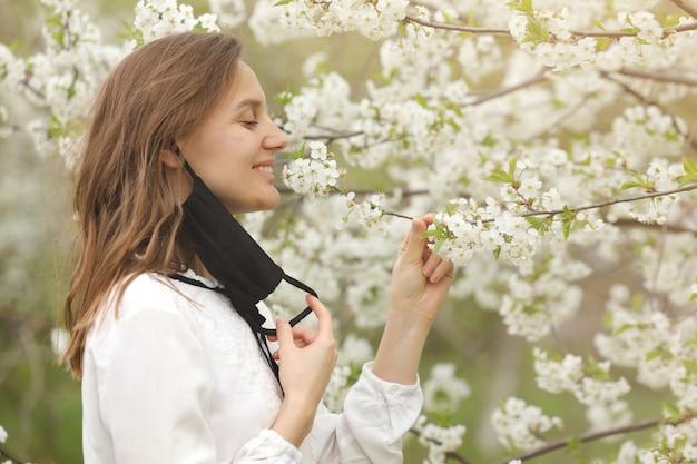 Hermosa niña feliz se quitó la máscara médica para respirar el olor a flores