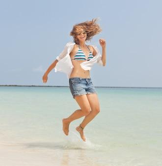 Hermosa niña feliz saltando en la playa