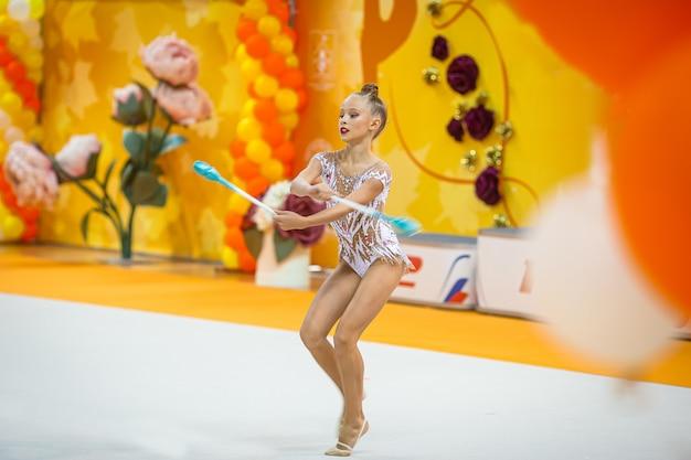 Hermosa niña gimnasta activa con su actuación en la alfombra