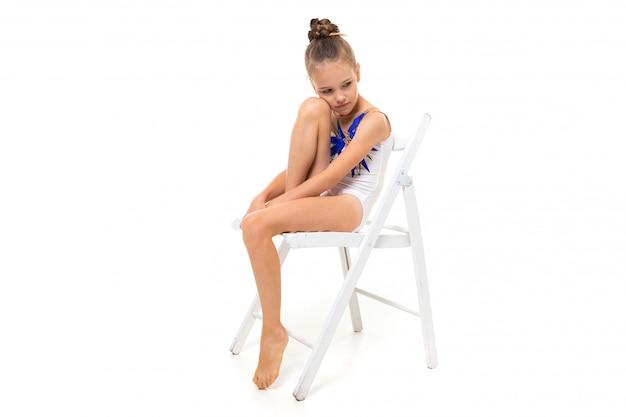 Hermosa niña gimnasta en medias hacer algunos ejercicios aislados sobre fondo blanco.
