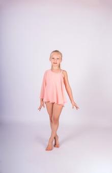 Una hermosa niña gimnasta en traje de baño deportivo se encuentra en una pared blanca aislada