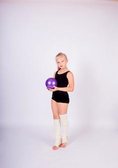 Una hermosa niña gimnasta en un traje de baño negro y mallas blancas se encuentra con una pelota en una pared blanca aislada con espacio para texto