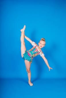 Una hermosa niña gimnasta en un traje se encuentra en una pose para el equilibrio en una pared azul aislada