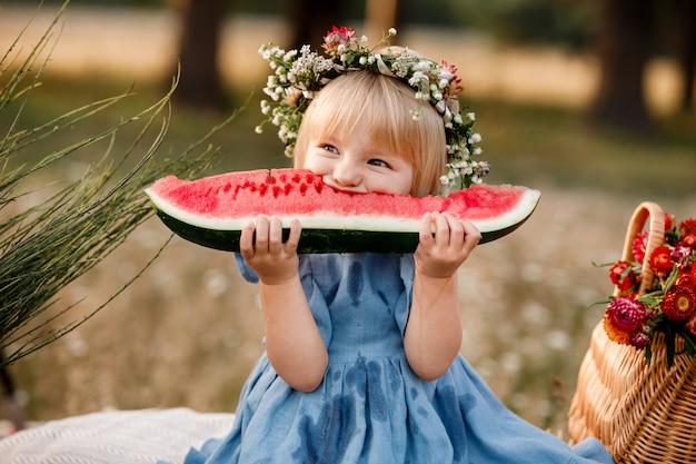 Hermosa niña en guirnalda floral está comiendo sandía en el parque de verano