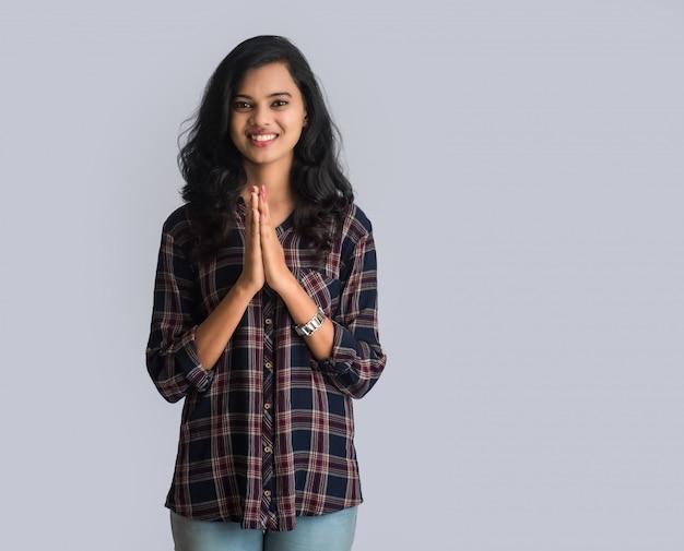 Hermosa niña india con expresión de bienvenida o invitando o saludando a namaste