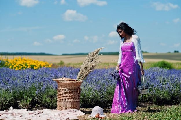 Hermosa niña india usa sari vestido tradicional de la india en campo de lavanda púrpura con canasta.