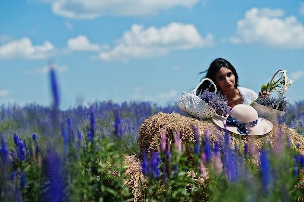 Hermosa niña india usa sari vestido tradicional de la india en campo de lavanda púrpura.