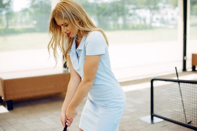 Hermosa niña jugando al golf en un campo de golf