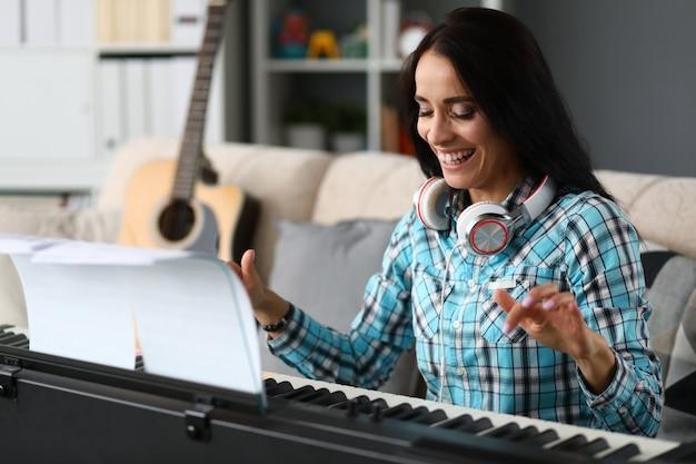 Hermosa niña jugando sintetizador en casa y riendo