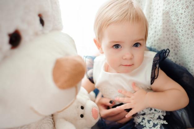 Hermosa niña con juguete sonriendo a la cámara