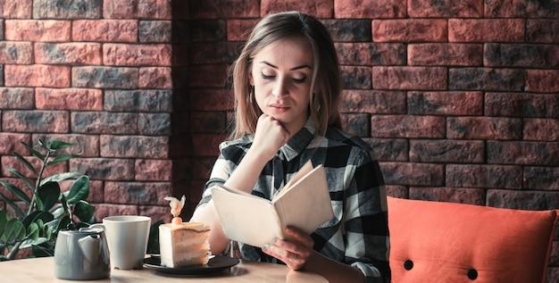 Hermosa niña lee un libro en un café