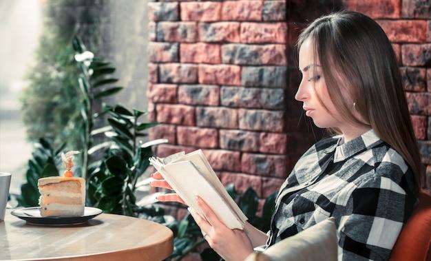Hermosa niña leyendo un libro en un café